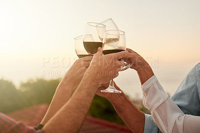 Buy stock photo Shot of a group of unrecognizable people having a celebratory toast with wine outside during sunset