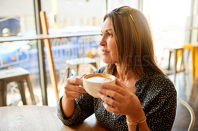 Buy stock photo Shot of a mature woman looking thoughtful while having coffee at a cafe