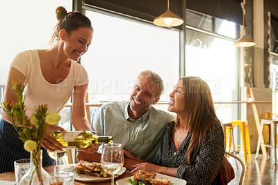 Buy stock photo Shot of a young woman serving a mature couple at a restaurant