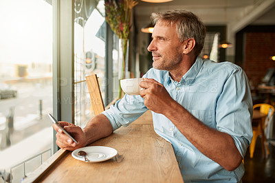 Buy stock photo Shot of a mature man using a mobile phone while having coffee at a cafe