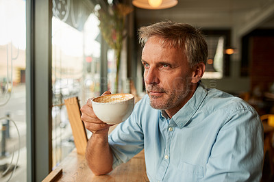 Buy stock photo Shot of a mature man looking thoughtful while having coffee at a cafe