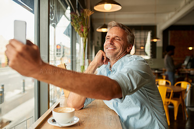 Buy stock photo Shot of a mature man taking a selfie at a coffee shop