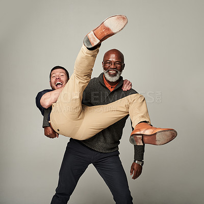 Buy stock photo Studio shot of two mature men goofing around against a grey background
