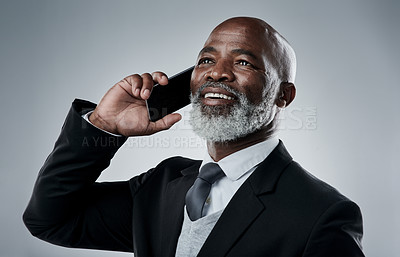 Buy stock photo Studio shot of a mature businessman talking on a cellphone against a grey background