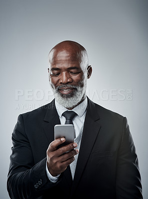 Buy stock photo Studio shot of a mature businessman using a cellphone against a grey background