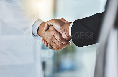 Buy stock photo Cropped shot of a doctor shaking hands with a businessman in a hospital