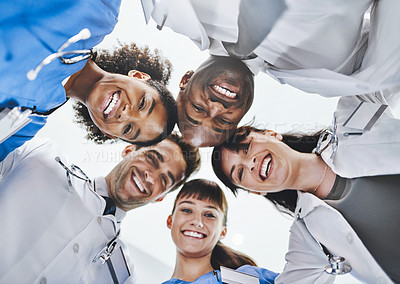 Buy stock photo Low angle portrait of a diverse team of doctors huddled together in a hospital