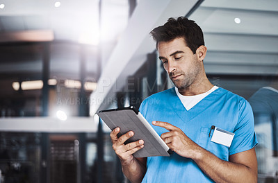 Buy stock photo Cropped shot of a young handsome male medical practitioner working in a hospital