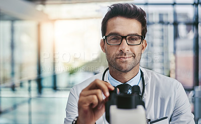 Buy stock photo Portrait of a young handsome male scientist working in a lab with a microscope