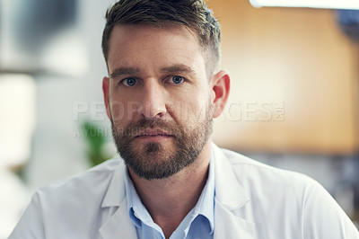 Buy stock photo Cropped portrait of a handsome male doctor sitting in his office