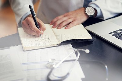 Buy stock photo High angle shot of an unrecognizable male doctor writing in his diary while sitting in his office