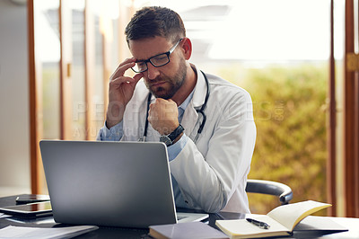 Buy stock photo Cropped shot of a handsome male doctor working on his laptop while sitting in his office
