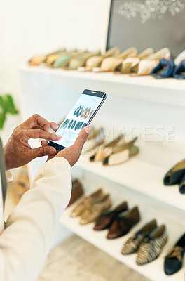 Buy stock photo Shot of an unrecognizable woman taking pictures on her cellphone while out shopping