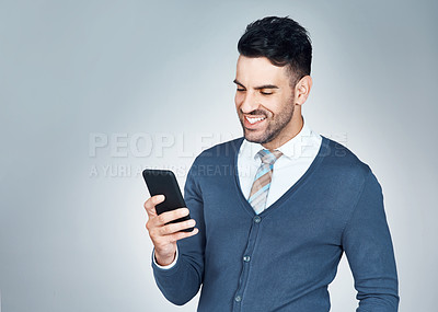 Buy stock photo Studio shot of a handsome young businessman using a cellphone against a grey background