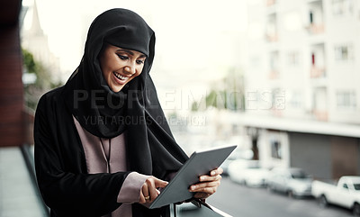Buy stock photo Cropped shot of an attractive young businesswoman dressed in Islamic traditional clothing using a tablet while standing on her office balcony