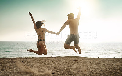 Buy stock photo Rearview shot of a young couple jumping into mid-air at the beach