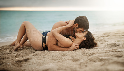 Buy stock photo Shot of a young couple kissing on the beach