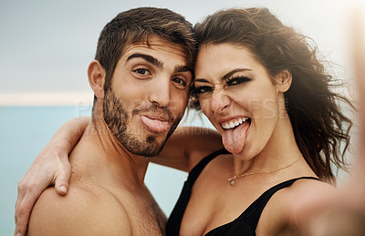 Buy stock photo Cropped shot of a young couple taking a selfie at the beach