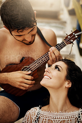 Buy stock photo Shot of a young couple playing the ukulele on the beach