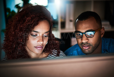 Buy stock photo Shot of two colleagues working late on a computer in an office