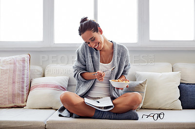 Buy stock photo Shot of a beautiful young woman talking on a mobile phone and working while having breakfast at home