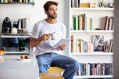 Buy stock photo Shot of a handsome young man using a digital tablet and having coffee in the morning at home