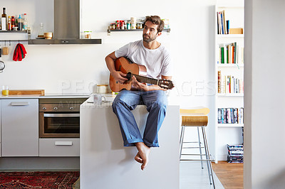 Buy stock photo Shot of a handsome young man playing the guitar in the morning at home