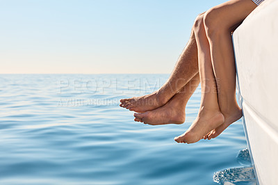 Buy stock photo Cropped shot of a couple sitting with their feet off the side of boat on a cruise