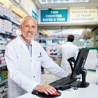 Buy stock photo Portrait of a mature pharmacist working on a computer in a chemist