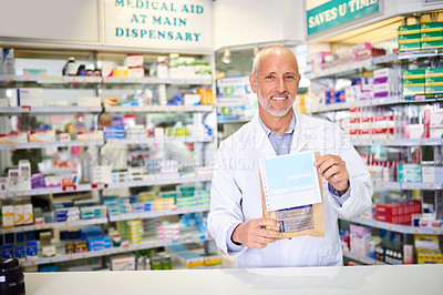 Buy stock photo Portrait of a mature pharmacist holding a paper bag with medication in a chemist