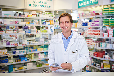 Buy stock photo Portrait of a young pharmacist writing on a clipboard in a chemist