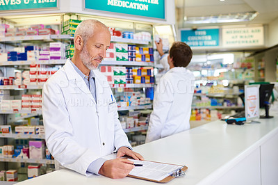 Buy stock photo Shot of a mature pharmacist writing on a clipboard in a chemist