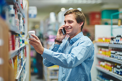Buy stock photo Cropped shot of a handsome young man making a phonecall while looking for medication in a pharmacy