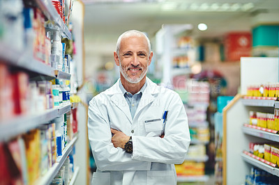 Buy stock photo Cropped portrait of a handsome mature male pharmacist standing with his arms crossed in the pharmacy