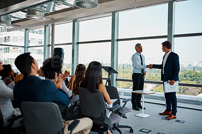 Buy stock photo Full length shot of two businessmen shaking hands in front of an audience during a seminar