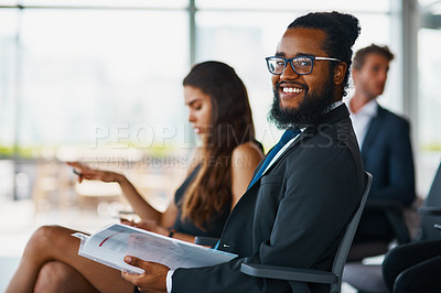 Buy stock photo Portrait of a handsome young businessman reading through some paperwork during a seminar in the conference room