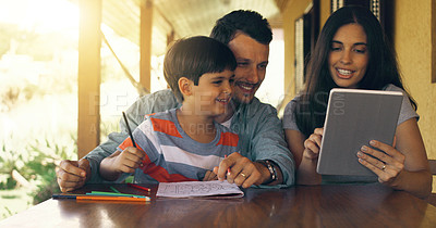 Buy stock photo Cropped shot of a young family colouring in and using a tablet by the table outside
