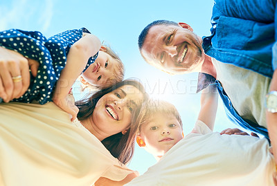 Buy stock photo Low angle shot of a happy family bonding together outdoors