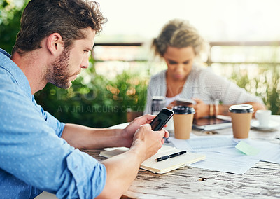 Buy stock photo Shot of a young businessman using a cellphone outdoors with his colleagues in the background