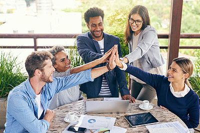 Buy stock photo Shot of a group of businesspeople high fiving during a meeting outdoors