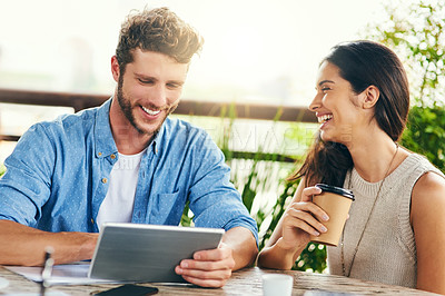Buy stock photo Shot of two businesspeople using a digital tablet together outdoors