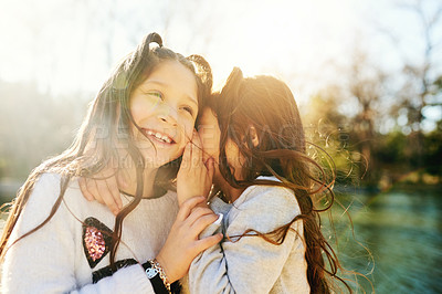 Buy stock photo Cropped shot of an adorable little girl whispering in her sisters ear outdoors