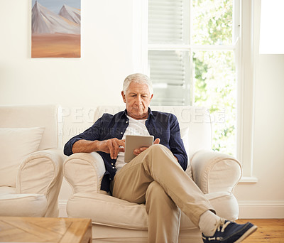 Buy stock photo Shot of a senior man using a digital tablet on the sofa at home