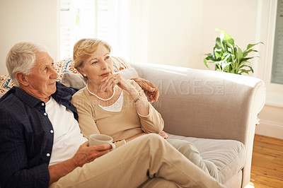 Buy stock photo Shot of a senior couple having a chat and coffee break on the sofa at home