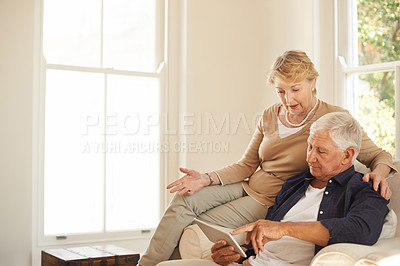 Buy stock photo Shot of a senior couple using a digital tablet together on the sofa at home