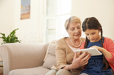 Buy stock photo Shot of a little girl using a digital tablet with her grandmother on the sofa at home