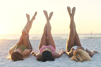 Buy stock photo Shot of unrecognizable female best friends relaxing on the sand at the beach