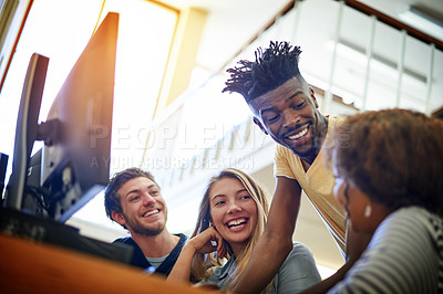 Buy stock photo Shot of a group of university students working together on a computer in the library at campus