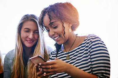 Buy stock photo Shot of two university students using a cellphone at campus