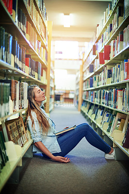 Buy stock photo Shot of a university student sleeping between the bookshelves in the library at campus